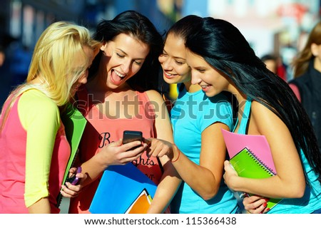 group of female students chatting in social network on mobile phone - stock photo