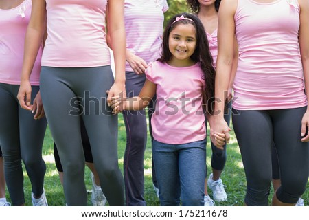 Group of female volunteers supporting breast cancer campaign in park - stock photo