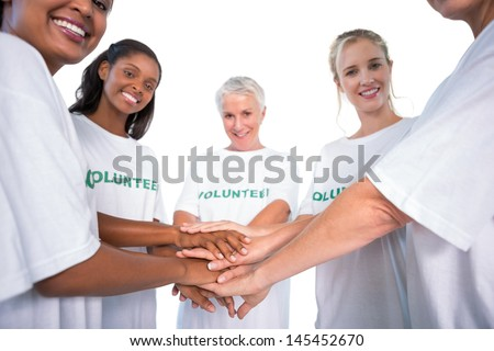 Group of female volunteers with hands together smiling at camera on white background