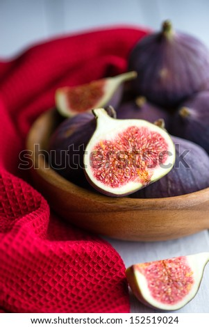 Group of figs in a bowl and on rustic blue wooden table