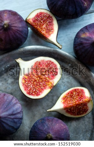 Group of figs in a bowl and on rustic blue wooden table - stock photo
