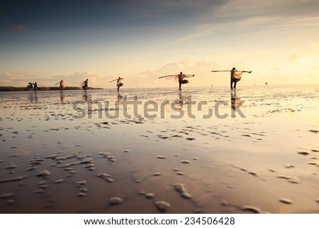 Group of fishermen are fishing on the beach in sunrise, Mekong Delta, Bac Lieu, Vietnam - stock photo