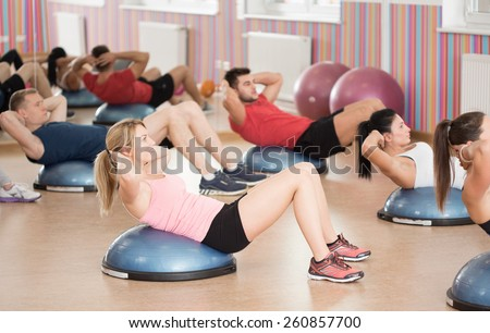 Group of fit people doing crunches on bosu - stock photo
