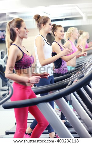 Group of fit women working out on treadmill in gym