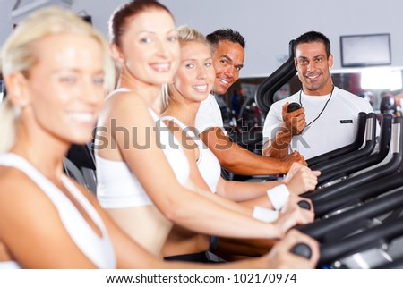group of fitness people and trainer in gym - stock photo