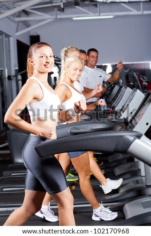 group of fitness people running on treadmill in gym - stock photo