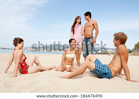 Group of five attractive teenagers enjoying a holiday break together, chatting and having fun while relaxing on a summer beach during a sunny day. Travel and recreational lifestyle.