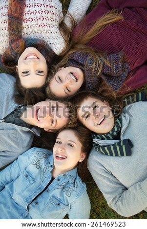 Group of five Caucasian teenagers laying down on grass together