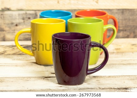 Group of five colorful cups on wooden background. - stock photo