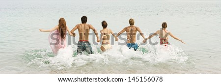 Group of five friends holding hands and running into the sea water together, being spontaneous and having fun while on a summer vacation on a beach with blue and turquoise waters. - stock photo