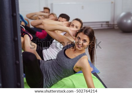 Group of five happy and attractive men and women doing abdominal toning exercises in gym