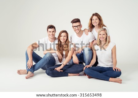 Group of Five Happy Young Friends In Casual Plain White Shirts and Jeans, Smiling at the Camera While Sitting on the Floor Against Off-White Background Inside the Studio. - stock photo