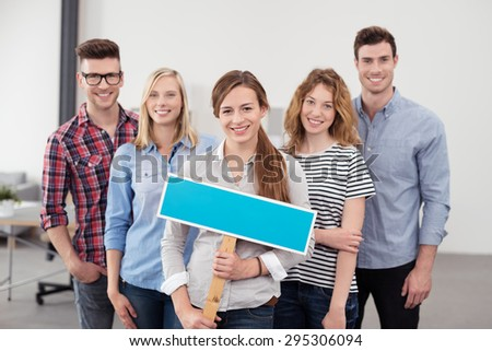 Group of Five Happy Young Office Employees with Empty Blue Green Placard, Looking at the Camera. - stock photo