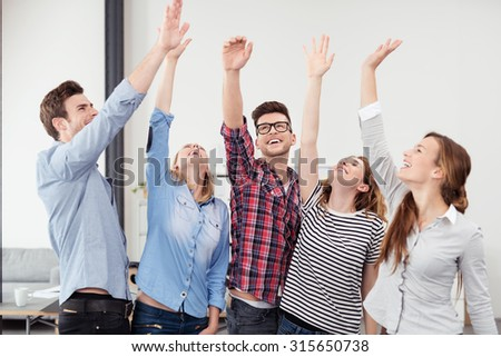 Group of Five Happy Young Office Worker with Hands in the Air Hoping for Success on their Plans.