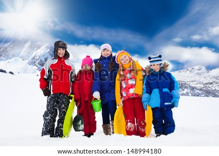 Group of five kids standing outside in snow with mountain on background