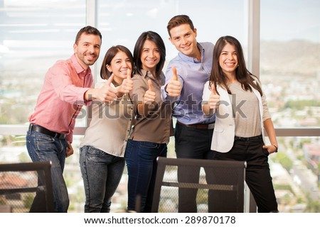 Group of five Latin people in casual attire giving their thumbs up and smiling - stock photo