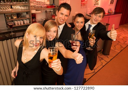 Group of five people drinking and celebrating in a bar - stock photo