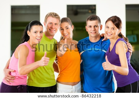 Group of five people exercising in gym or fitness club - stock photo