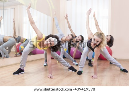 Group of Five Professional Sportswomen Making Stretching Exercises with Trunk Bending in Sport Class. Horizontal Image Orientation - stock photo