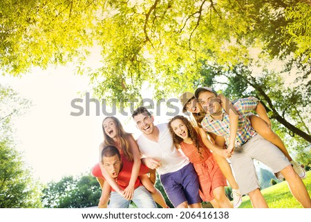 Group of five teenage friends having fun in park - stock photo