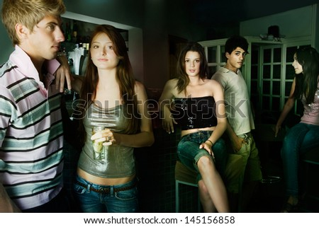 Group of five young people socializing going out during the evening in a night club, meeting, drinking and chatting. - stock photo