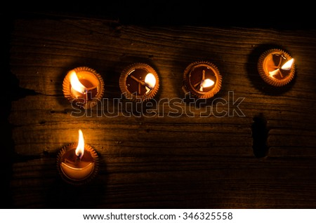 group of flame light on small pottery candle base. object's on wood floor in dark area. black background color. - stock photo