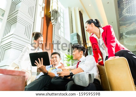 Group of four Asian Chinese businesspeople meeting for small team discussion in luxurious hotel lobby, there are documents on a tablet computer  - stock photo