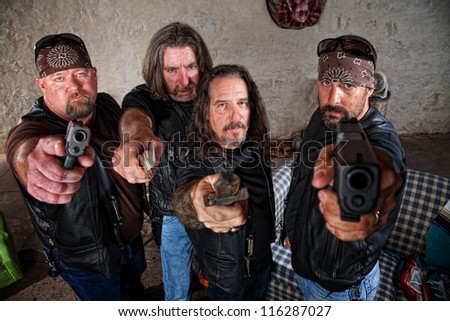 Group of four bikers in leather jackets brandishing weapons