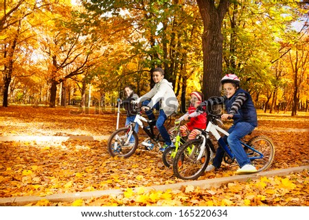 Group of four black boys and girl, brothers and sister riding bicycles and scooter in the autumn October park with maple leaves - stock photo