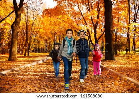 Group of four black boys and girl, happy brothers and sister 3-10 years old going together holding hands in the park wearing backpacks and autumn clothes in maple park - stock photo