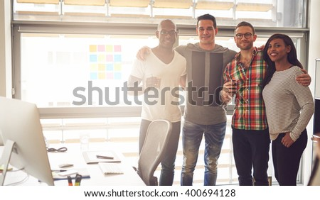 Group of four Black, Caucasian and Hispanic happy adults wearing casual clothing and holding drinks while standing and embracing each other in office with large bright window - stock photo