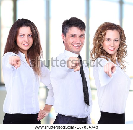Group of four business people in a row pointing