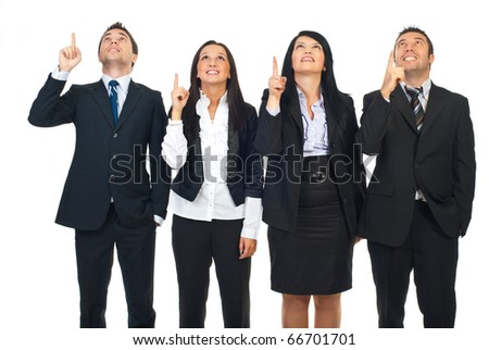 Group of four business people in a row pointing and looking up to copy space isolated on white background