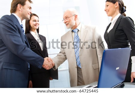 Group of four business people shaking hands in an office