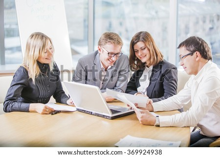 Group of four business people working on laptop at meeting, business people working together in meeting room - stock photo