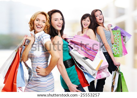 Group of four cheerful adult girls with  purchases in the colored bags