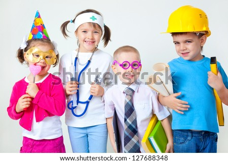 Group of four children dressing up as professions - stock photo
