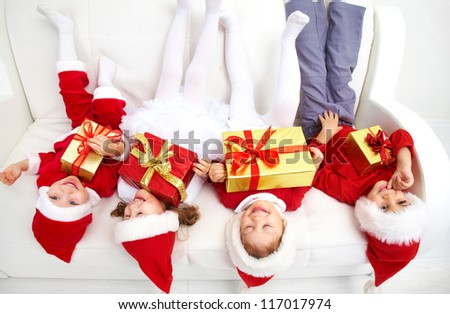 Group of four children in Christmas hat on sofa head over heels - stock photo