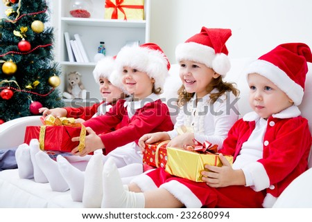 Group of four children in Christmas hat with presents on couch - stock photo