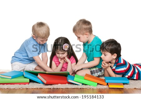 Group of four children with books on the floor