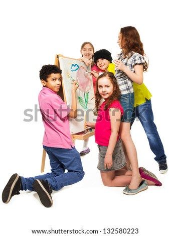 Group of four diverse kids, boys and girls painting image together with paintbrushes on the white canvas