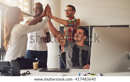 Group of four diverse men and women in casual clothing celebrating an important milestone while relaxing in office near large bright window - stock photo