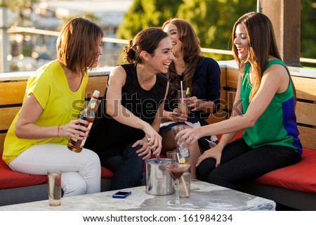 Group of four female friends having fun and drinking alcohol in a terrace in the afternoon - stock photo