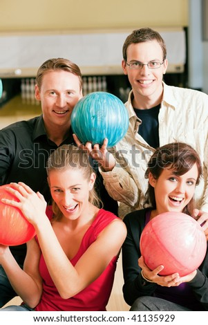 Group of four friends in a bowling alley having fun, holding their bowling balls (focus on girls in front row)