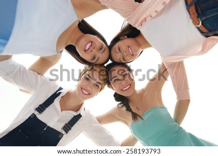 Group of four friends in circle hugging and looking at the camera