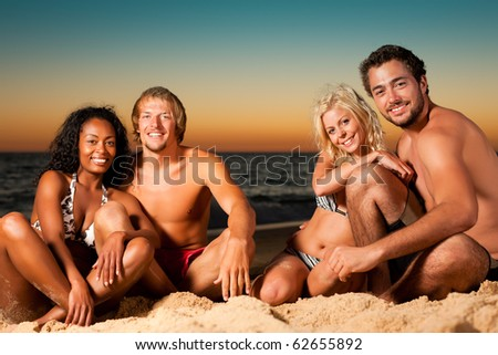 Group of four friends - men and women - sitting on the beach against the afterglow of a sunset over the ocean
