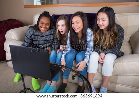 Group of four friends watching streaming tv show on laptop compu