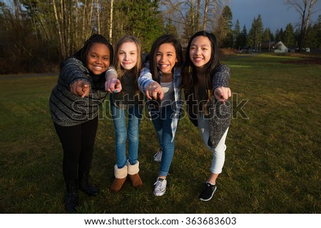 Group of four girls pointing fingers and smiling