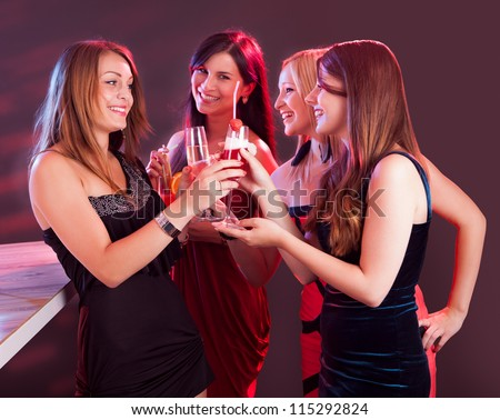 Group of four happy beautiful young female friends celebrating in a nightclub with glasses of cocktail in their hands