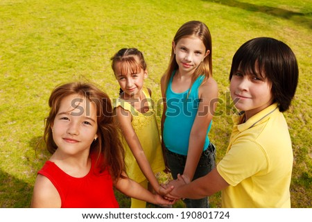 Group of four  happy children illustrating teamwork outdoors. - stock photo
